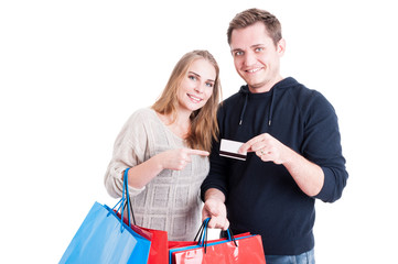 Couple holding shopping bags pointing on credit card