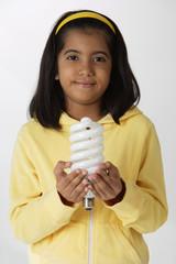Girl holding light bulb