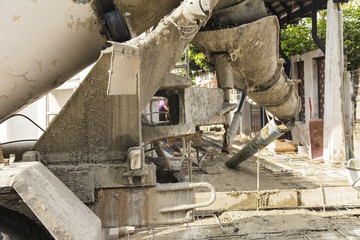 Cement truck is pouring cement into a foundation with constructi