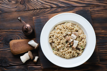 Risotto with porcini over rustic wooden background, top view