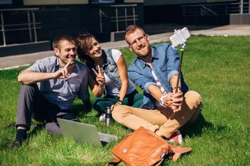 Group of happy friends taking a selfie on  blue sky in campus lawn, caucasian