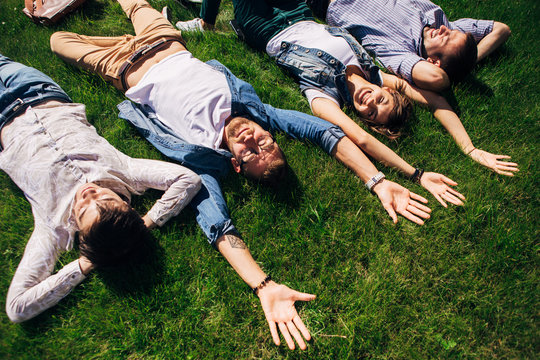 four students lying on the grass