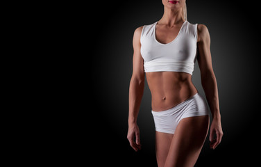 Isolated cropped portrait of female bodybuilder ready for gym exercise. Horizontal shot with copy space on black background.