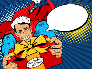 Pop art Christmas man. Young handsome man in superhero costume and Santa Clause hat flies with big Christmas gift from Santa and speech bubble. Vector illustration in retro pop art comic style.