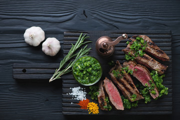 Grilled rump steak with chimichurri on a black wooden background