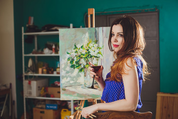 Creative pensive painter girl paints a colorful picture on canva