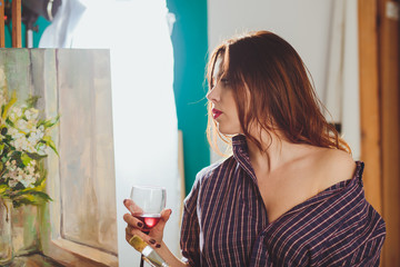 Woman artist painting a picture in a studio. Creative pensive pa