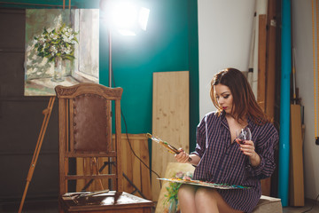 Woman artist painting a picture in loft studio.
