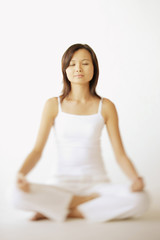 Young woman sitting in lotus position, eyes closed