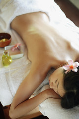 Young woman lying on massage table, eyes closed