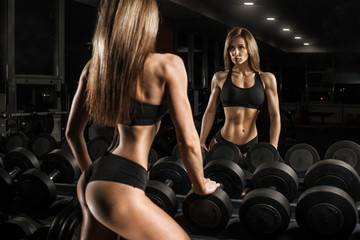 Fitness girl with dumbbells in front of the mirror
