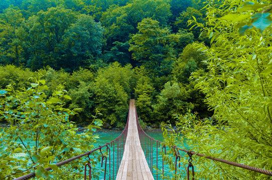 Suspension bridge over the stormy mountain river