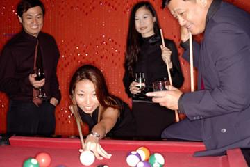 Men and women playing pool