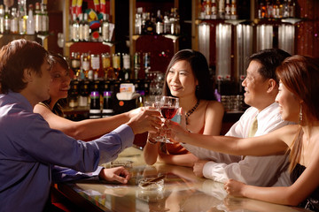 Group of people sitting around table toasting