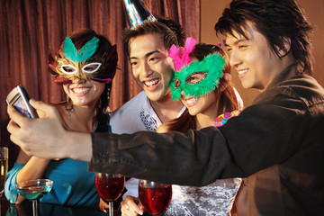 Couples with mask and hat using camera phone to take a picture