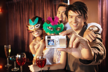 Couples with masks taking a picture with camera