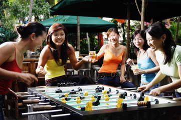 Group of young women playing foosball