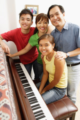 Family with two children, standing around piano, portrait