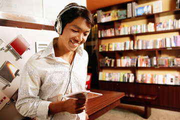 Young man listening to music, smiling, looking down at CD