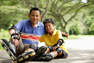 Father and son, sitting in park, wearing roller blades
