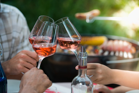 Happy friends having fun outdoors, hands toasting rose wine glass