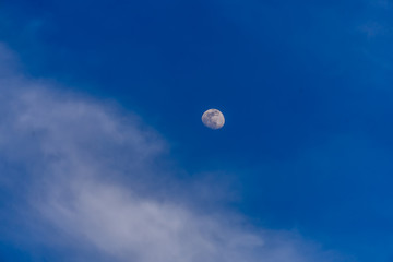 Moon and blue sky with some white clouds.