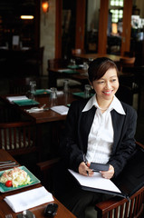 Businesswoman in restaurant, holding pen and folder, looking away, smiling