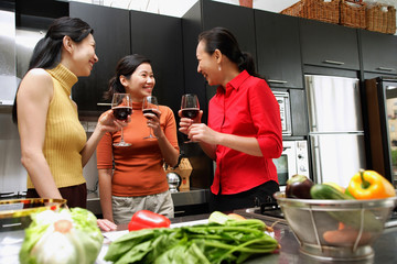 Three women in kitchen, holding wine glasses, talking