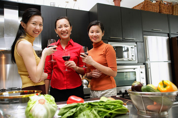 Three women in kitchen, holding wine glasses, looking at camera