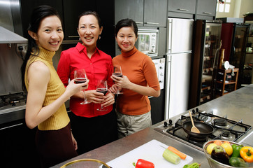 Three women in kitchen, holding wine glasses, smiling at camera