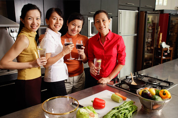 Four women in kitchen, holding wine glasses, smiling at camera