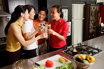 Women in kitchen, holding wine glasses, toasting