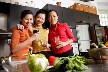 Women in kitchen, standing side by side, smiling at camera