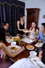 Couples having dinner at home, woman serving food