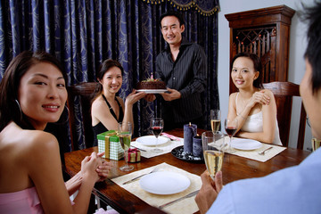 Friends at home, man and woman holding cake, looking at camera