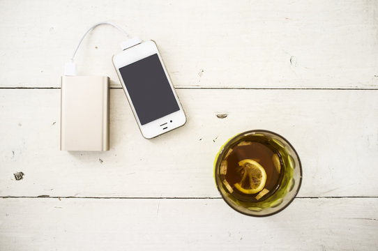Smartphone being charged from a portable charging device, nearby there is a incomplete glass of tea with lemon