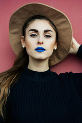 Young girl with hat, black sweater and blue lipstick
