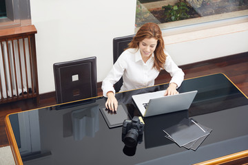 Attractive female photographer sitting back in her chair smiling in satisfaction at her captures as she looks at the screen of her laptop with her camera nearby