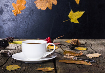 White coffee cup on the old wooden board with yellow leaves and falling leaves with rain in the background