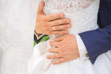 Close up of male hands with golden ring on finger tenderly with love hugging his bride around her waist. Happy wedding couple kissing after ceremony. Horizontal color photography.