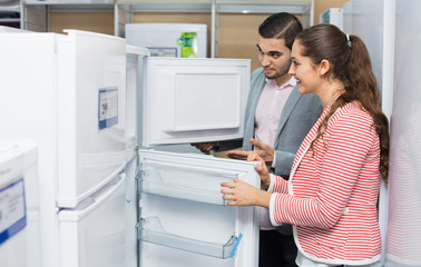 Young smiling couple looking at large fridges