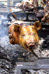 Whole carcass of a pig roasting on the grill