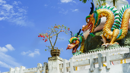 Colorful dragons statue with blue sky, Thailand.