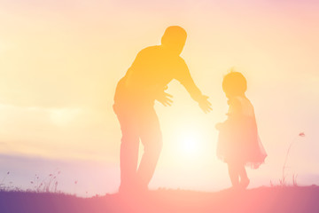 Father took the baby learn to walk at sunset.