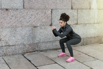 Sporty woman doing warm up squat, stretching near a wall