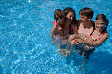 Happy family having fun in swimming pool on summer vacation, parents and kids