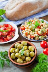 Mediterranean salad board -  green olives, chickpea, basil, toma