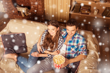 Attractive couple watching tv with popcorn on xmas night