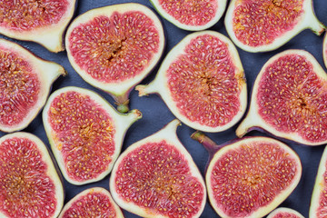 Pieces of fig on a stone board. Fruit background
