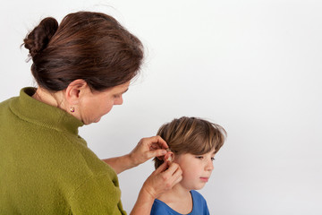 Audiologist woman fitting a young boy with a hearing aid